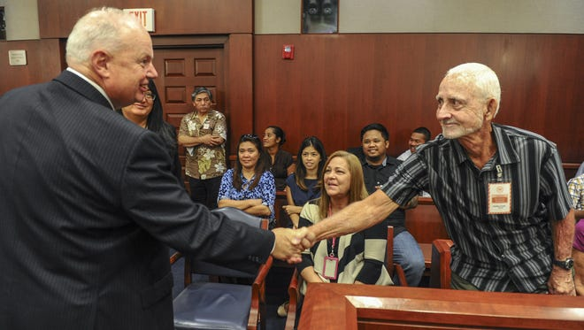 "In this Aug. 27, 21016, file photo, Arnold ""Dave"" Davis, right, shakes hands with Ninth Circuit Court of Appeals Circuit Judge N. Randy Smith prior to the start of an appeal hearing at the U.S. District Court in Hagåtña."