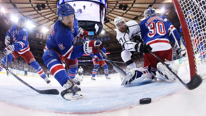 Rangers defenseman Anton Stralman, left, reaches to save the puck from crossing the goal line as Los Angeles Kings center Jeff Carter, right, tries unsuccessfully to reach around goalie Henrik Lundqvist and knock the puck into the net in the first period of Game 4.