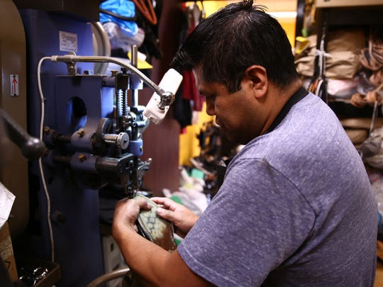 Refugio Contreras restitches the sole of a shoe that has come loose at C&F Shoe Repair in the City of Poughkeepsie on Friday, Feb. 9, 2018.