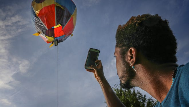 DJ Stickler takes a photo of a miniature hot air balloon, his 50th, that he pieced together in barn at his home in southern Jefferson County.  Stickler, 23, creates the hot air balloons from plastic garbage bags and duct tape. August 22, 2016