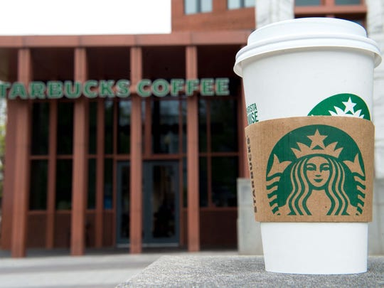 A Starbucks coffee cup is seen outside a Starbucks