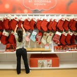 Megan Shoemaker of Fairless Hills, Pa., works on a Christmas stocking display at Kohl's in Yardley, Pa., on Oct. 2. According to the National Retail Federation, holiday spending is expected to be up only marginally.