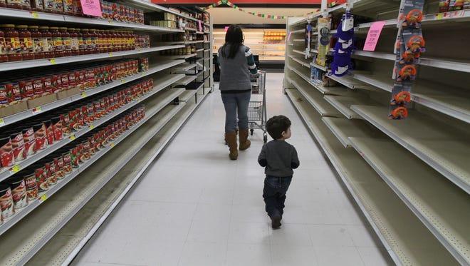 Joshua Hoad, 2, of Farmington follows his mother, Shannon, as they walk through an aisle.  Wade's Market Center on Route 96 in Farmington, Ontario county is closing after 47 years in business.