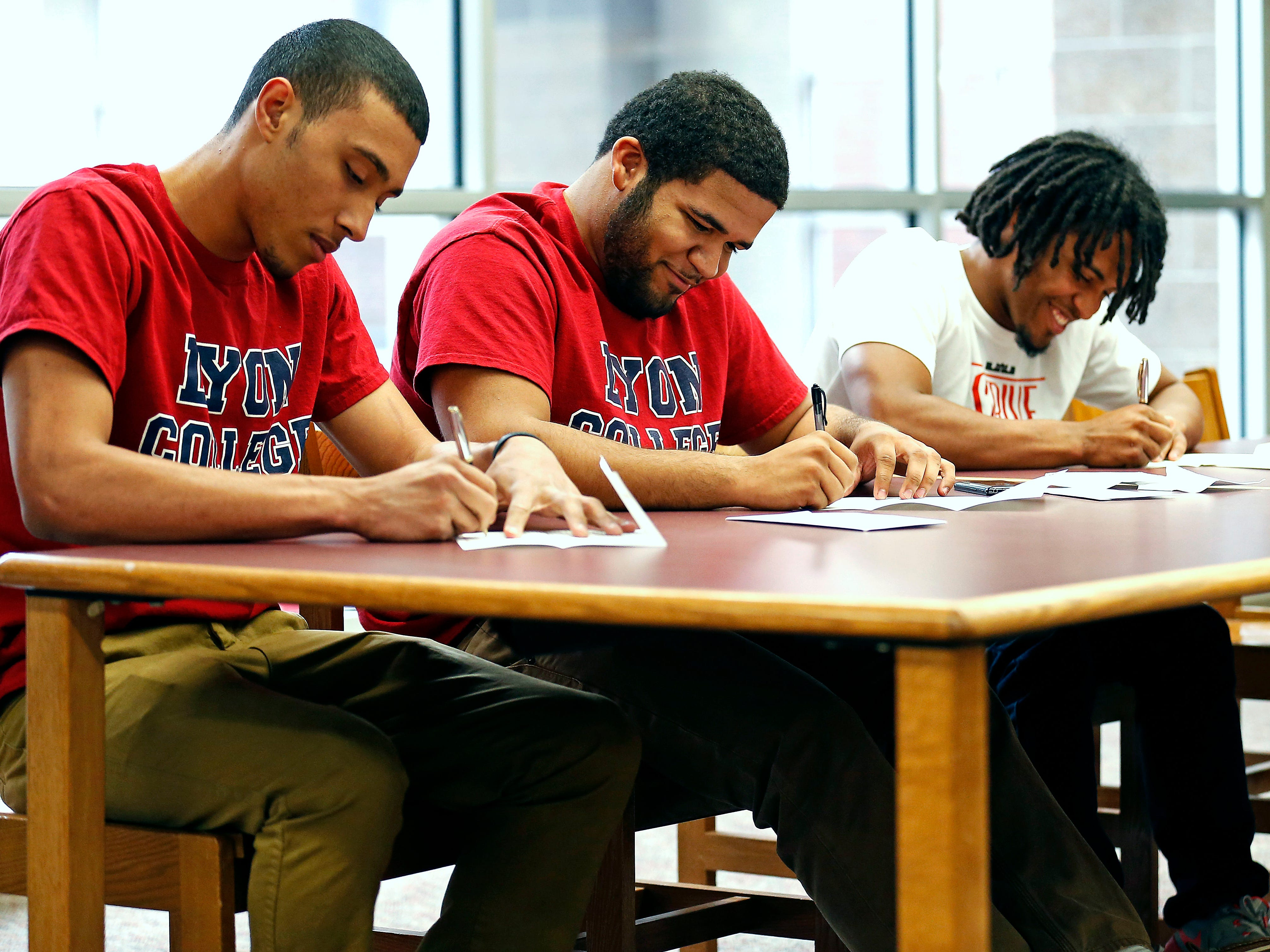 Central High School seniors (from left) Isaiah Holyfield, Jordan Johnson and Javiaun King sign letters of intent at the Central High School library on Tuesday as they commit to attend and play football for Lyon College starting next fall.