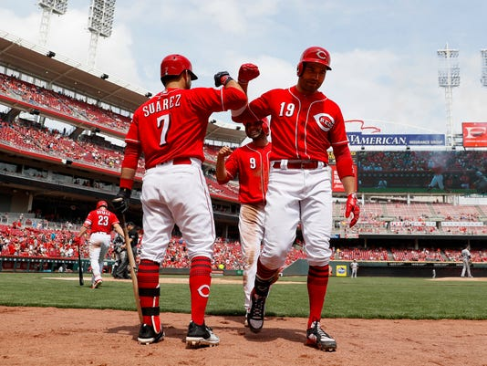 Cincinnati Reds' Joey Votto (19) celebrates with teammate Jose Peraza (9) and Eugenio Suarez (7) after hitting a two-run home run off Colorado Rockies starting pitcher Kyle Freeland in the sixth inning of a baseball game, Sunday, May 21, 2017, in Cincinnati. (AP Photo/John Minchillo)