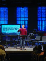 Kyle Idleman, the Southeast Christian's teaching pastor, appears before members of the Crestwood congregation through a large-screen broadcast.