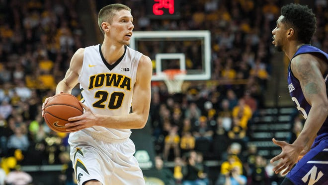 Mar 7, 2015; Iowa City, IA, USA; Iowa Hawkeyes forward Jarrod Uthoff (20) is defended by Northwestern Wildcats guard JerShon Cobb (23) during the first half at Carver-Hawkeye Arena. Mandatory Credit: Jeffrey Becker-USA TODAY Sports