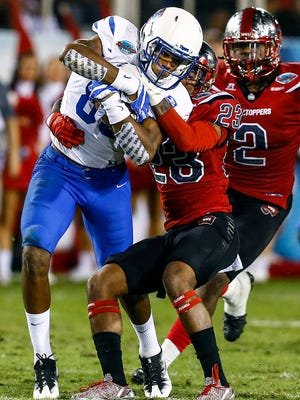 University of Memphis receiver Daniel Hurd (left) battles Western Kentucky University defender De'Andre Simmons (middle) for a first down as Keith Brown (right) helps on the play during first quarter action in the Boca Raton Bowl in Florida.