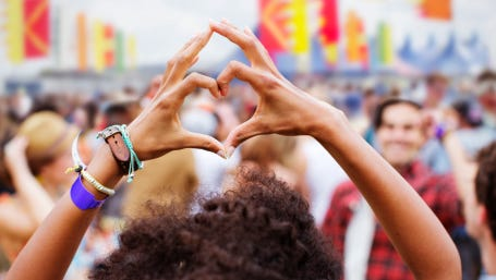 Woman forming heart-shape with hands at music festival