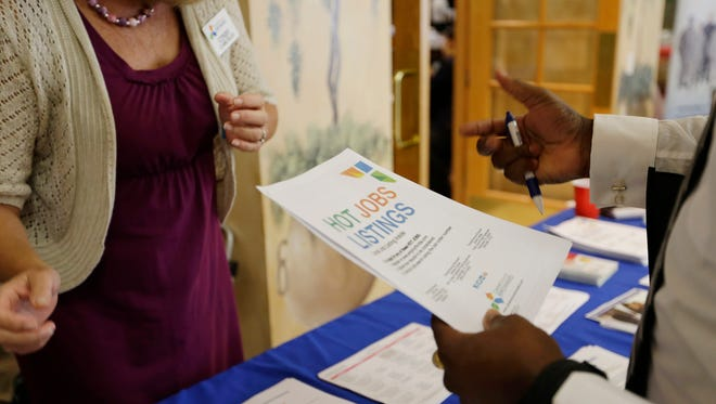 A military veteran, right, talks Oct. 6, 2015, with a veterans outreach representative about employment opportunities, at a job fair for veterans in Pembroke Pines, Fla.