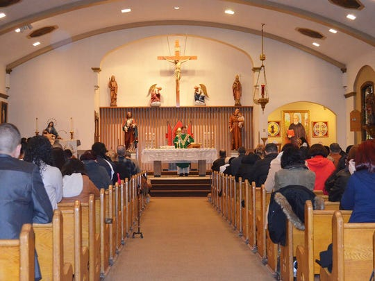 The 12 noon Sunday Spanish Mass, celebrated by Fr. Michael W. Rothan, pastor of St. Benedict the Abbot Church, usually draws a standing-room-only congregation.