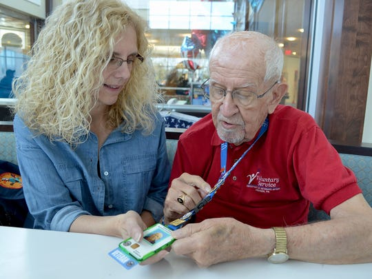 Bob Boyer gives his daughter-in-law to be, Barbara Kirschner, the stories behind each of the pins that he proudly wears on the lanyard of his VAMC identification badge. He attached the word VETERAN to the bottom of the badge as a point-in-common with Veterans coming to the center.