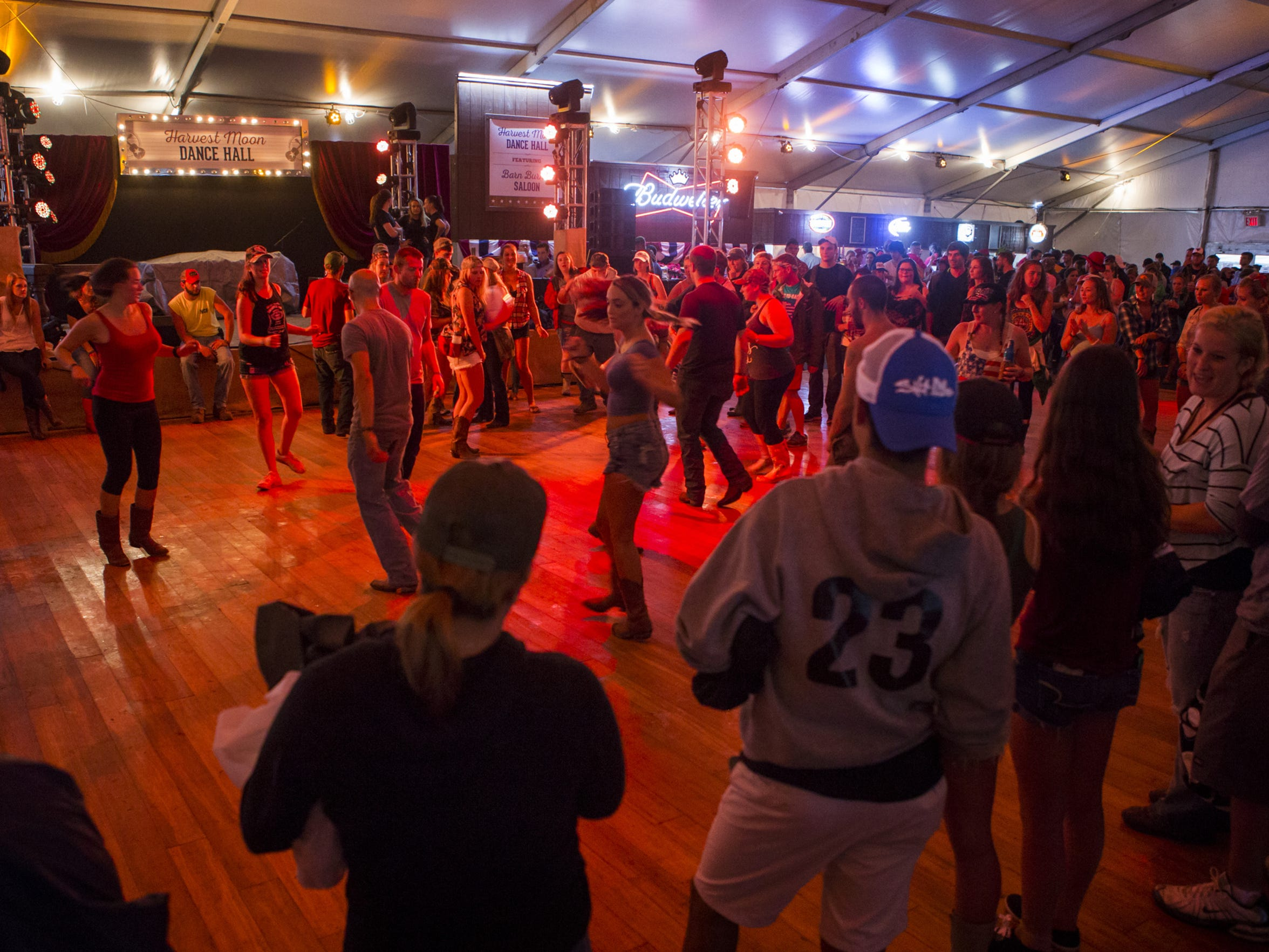 Spectators gather around line dancers in the Harvest Moon Dance Hall at the Big Barrel Country Music Festival in Dover last summer.