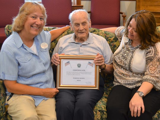 Harold Mohn, who turns 100 on Aug. 28, explains to Juniper Village Executive Director Joan-Marie Norman, left, and Christine Heibel, right, the village's director of community relations, the certificate that accompanies the flag that was flown in his honor over the American Cemetery at Omaha Beach, France, on April 11, 2005.