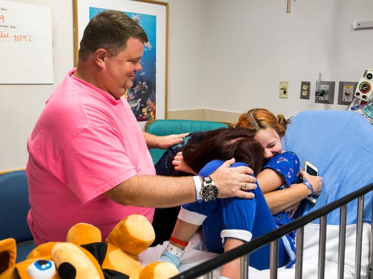 Emily Ruckle gets a hug from her mother Maria and father Todd before heading in for surgery at the Children's Hospital of Philadelphia on Friday morning, August 19, 2016.