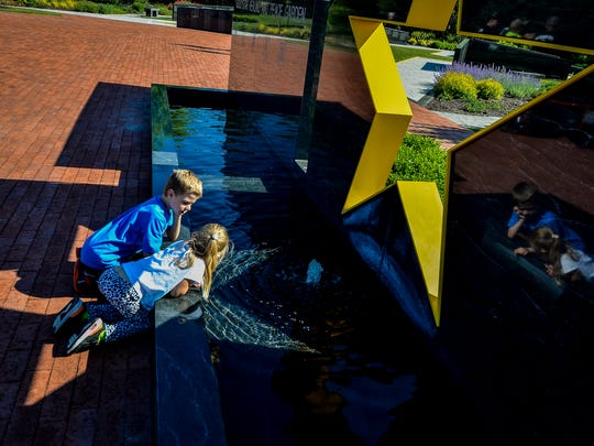 Jaden Brown, 8, and sister Kya, play in the fountain