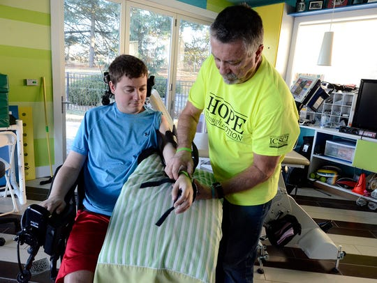 Steve Keefer helps his son Brian with a MyoPro electronic