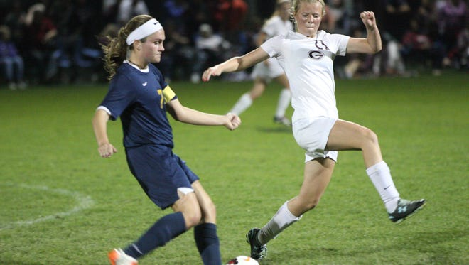 Woodmore's Lily Rothert looks for a teammate as Genoa's Hannah Rowland tries to intercept.