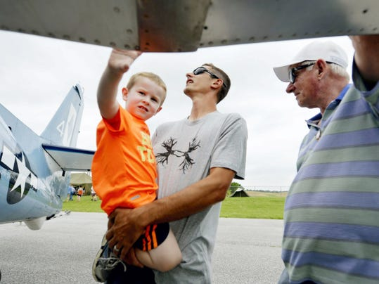 Brett Herbert of Fawn Township holds his son Ryan, 3, as he and his father-in-law Gerry Kopp of West Manchester Township examine a 1945 TBM-3 Avenger belonging to the Mid-Atlantic Air Museum at the seventh annual Aviation Days at the York Airport in Jackson Township.