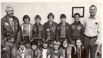Bill Earney (left), with Troop 18 in 1977 at a police station. Andy Wilson sits in the front row, third from the right.