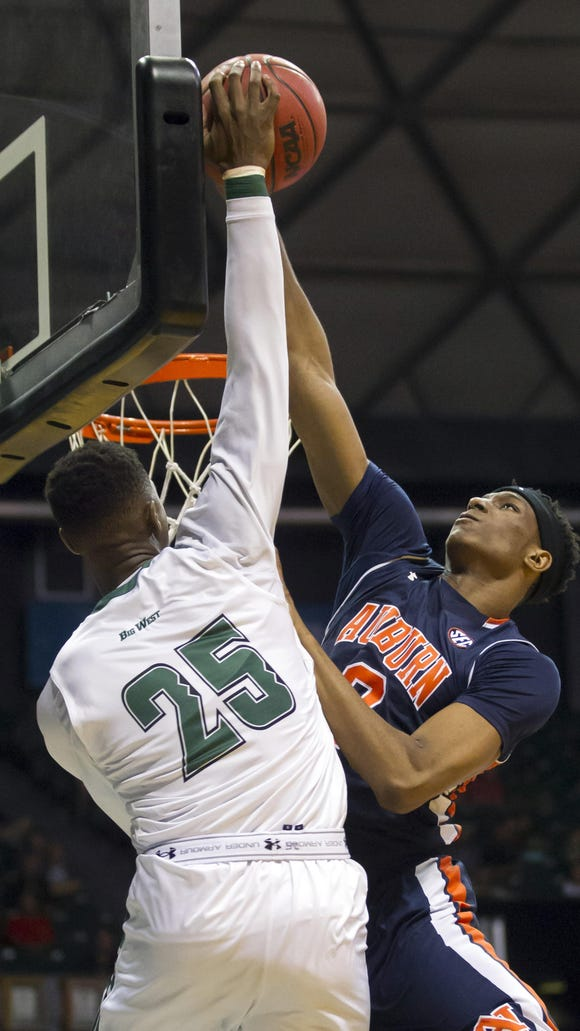 Auburn forward Horace Spencer, right, blocks a dunk attempt by Hawaii forward Michael Thomas, left, in the second half of an NCAA college basketball game at the Diamond Head Classic, Friday, Dec. 25, 2015, in Honolulu. Hawaii won 79-67. (AP Photo/Eugene Tanner)