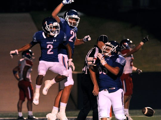 Cooper receiver Daelin Campos (2) celebrates with teammates Braden Hill (center) and Mateo Valero after Campos' touchdown against Grapevine on Friday, Sept. 8, 2017.