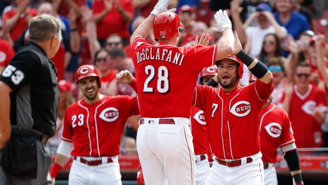 Cincinnati Reds' Anthony DeSclafani (28) celebrates with Eugenio Suarez (7) after hitting a grand slam off Chicago Cubs relief pitcher Brian Duensing in the third inning of a baseball game last Saturday at Great American Ball Park. The Reds have won 12 of their last 17 games. (AP Photo/John Minchillo)