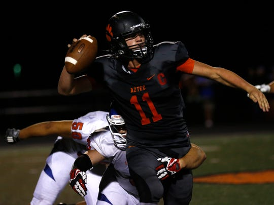 Aztec quarterback Cody Smith prepares to throw the ball before being taken down by the Los Lunas defense during Friday's game at Fred Cook Memorial Stadium in Aztec.