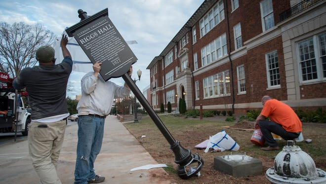 "Workers with Canam Signs and Imaging erect a sign in front of Clemson University's Riggs Hall, one of 11 such signs being placed in front of each building on campus that is on the National Register of Historic Buildings, Dec. 20, 2017. The campus improvements stemmed from a report adopted in February 2016 outlining recommendations developed by a board task force on the history of Clemson, which was charged with identifying ways to tell the university's complete history in a way that is ""forthcoming, accurate and beneficial to the Clemson family."""