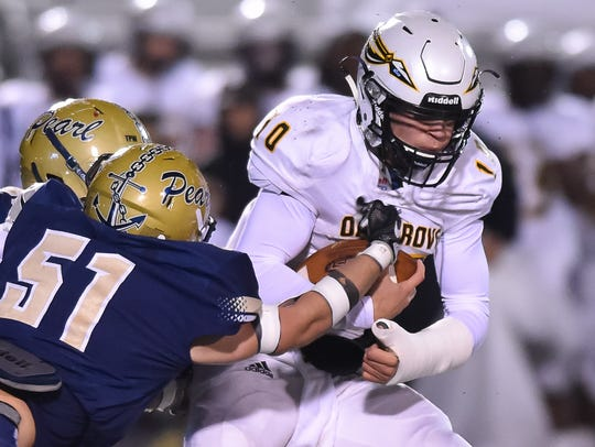 Pearl's Nathan Brewer brings down Oak Grove quarterback John Rhys Plumlee on Friday.