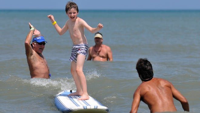 Spotters watch Jacob Forsman of Atlanta as he rides a wave during Surfers for Autism at Lori Wilson Park in Cocoa Beach.