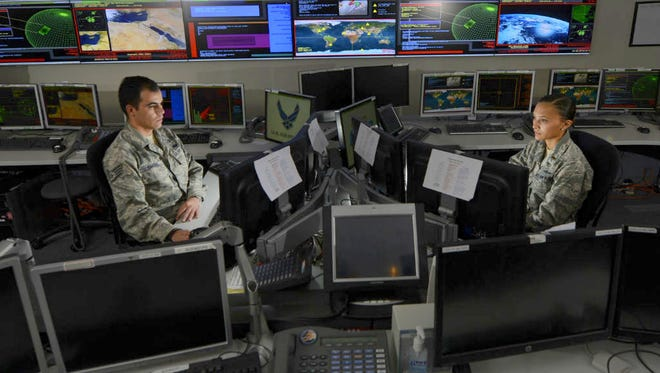 Airmen with the 721st Communication Squadron work in the Global Strategic Warning and Space Surveillance System Center at Cheyenne Mountain Air Force Station, Colorado, Sept. 2, 2014. Some airmen within communications squadrons have volunteered (or have been selected) for the Air Force's new initiative, Comms Squadron Next.