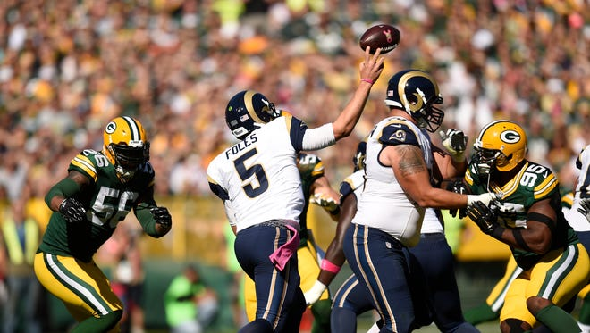 St. Louis Rams quarterback Nick Foles (5) throws under pressure from Green Bay Packers outside linebacker Julius Peppers (56) and defensive end Datone Jones (95) at Lambeau Field.