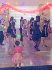 Line dancing at the family dance prompted a younger dancer to remove her shoes.