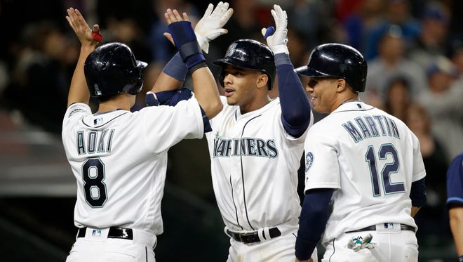 Seattle Mariners' Ketel Marte, right, is greeted by Norichika Aoki (8) and Leonys Martin (12) as Marte crosses home on his three-run home run against the Tampa Bay Rays in the sixth inning of a baseball game Monday, May 9, 2016, in Seattle. (AP Photo/Elaine Thompson)