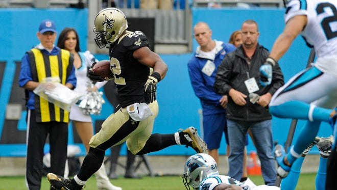 New Orleans Saints' Mark Ingram (22) runs past Carolina Panthers' Josh Norman (24) for a touchdown in the first half of an NFL football game in Charlotte, N.C., on Sunday.