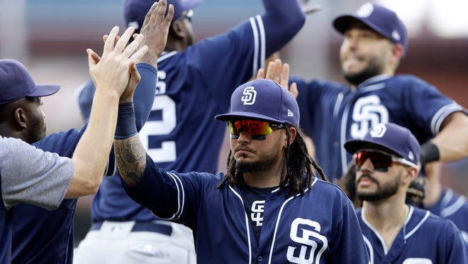 San Diego Padres' Freddy Galvis, center, celebrates with teammates after the first baseball game of a doubleheader against the Philadelphia Phillies, Sunday, July 22, 2018, in Philadelphia. (AP Photo/Matt Slocum)