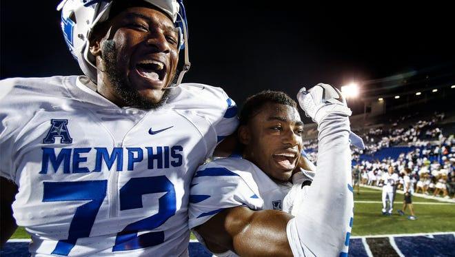 University of Memphis teammates Trevon Tate (left) and Chauncey Lanier (right) celebrate a 34-27 victory over Temple at the Liberty Bowl Memorial Stadium. Lanier ended the game with an interception.