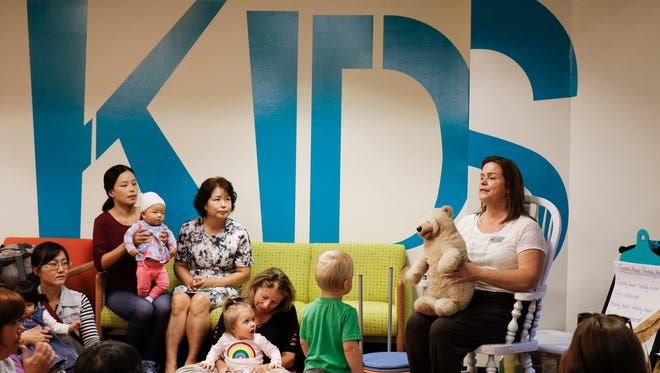 """East Lansing Public Library storyteller Tracey Pickard leads a sing-along Monday, Oct. 9, 2017,  to the song  """"Teddy Bear, Teddy Bear"""" before reading the story """"Little You"""" by Richard Van Camp."""