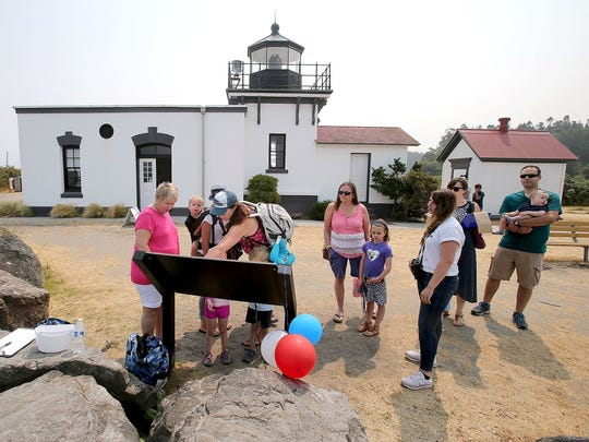 Donna Sandstrom, left, from the Whale Trail group explains about whales on the Whale Trail sign in front of the Point No Point lighthouse on Saturday during the National Lighthouse Day celebration.