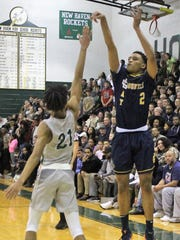 Country Day freshman Julian Roper launches a three-point shot over New Haven defender Jamir Farrior in the Class B regional title game.