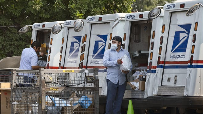 Postal workers load packages in their mail delivery vehicles at the Panorama city post office on Thursday, Aug. 20, 2020 in the Panorama City section of Los Angeles. On Saturday, the House passed a $25 billion spending plan for the USPS, but it's unlikely to pass the Senate.