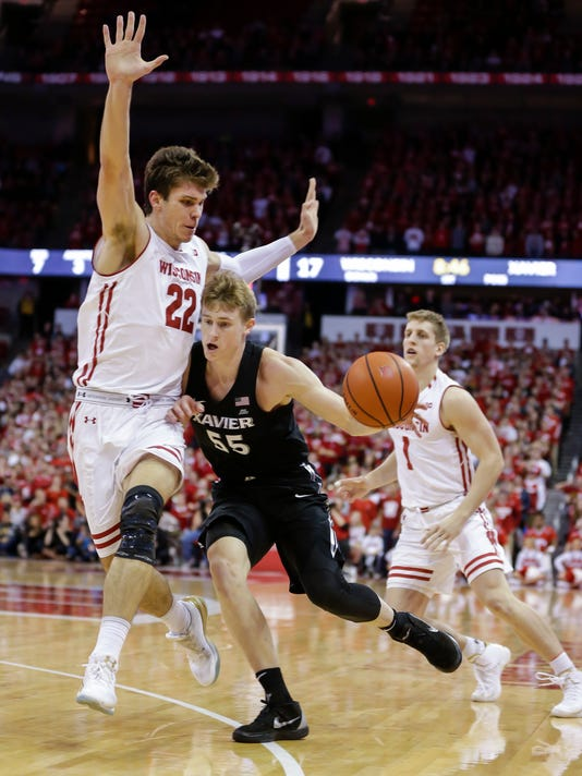Xavier's J.P. Macura (55) drives on Wisconsin's Ethan Happ (22) during the first half of an NCAA college basketball game Thursday, Nov. 16, 2017, in Madison, Wis. (AP Photo/Andy Manis)
