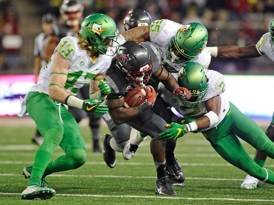 Oct 1, 2016; Pullman, WA, USA; Washington State Cougars running back Gerard Wicks (23) is brought down by Oregon Ducks defensive back Brenden Schooler (43), Oregon Ducks linebacker A.J. Hotchkins (55) and Oregon Ducks defensive back Tyree Robinson (2) during the second half at Martin Stadium. The Cougars won 51-33. Mandatory Credit: James Snook-USA TODAY Sports