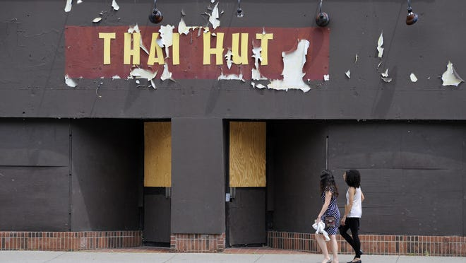Pedestrians walk past part of the vacant storefronts on West Grand River Avenue in East Lansing.