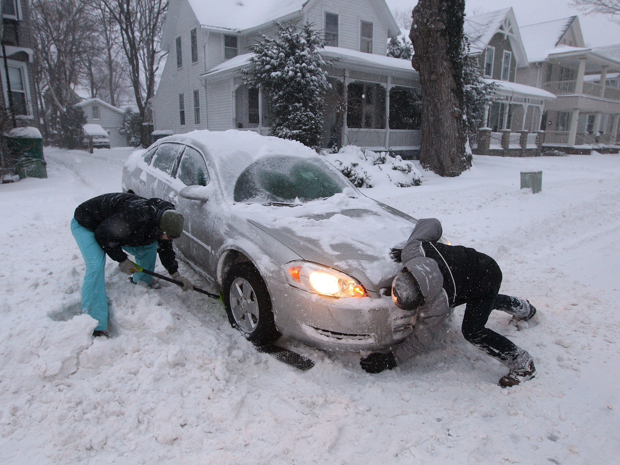 Matthew Kotula, right, got his car stuck in the snow on Cambridge Street and got some help from his neighbor Harry Weisberg with a shovel.