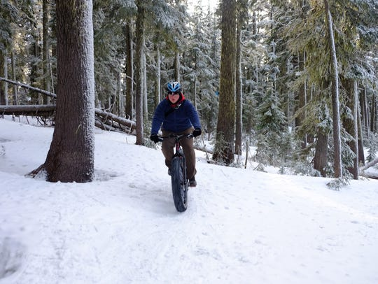 David Davis rides through the snow and trees on the