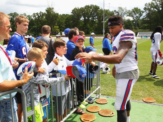 Andre Davie signs autographs as he leaves the field after practice.