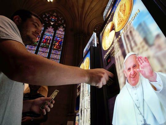 A man buys a souvenir medal with a picture of Pope Francis at a machine inside the Saint Patrick Cathedral in New York last month. Pope Francis will visit the U.S. on September 22-27, stopping in Washington, DC, New York, and Philadelphia.