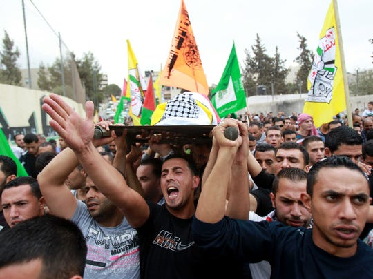 Mourners carry the body of 13-year-old Palestinian